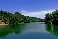 Una chiesa con il suo campanile sul lago del ` Alpi del dell di Castel Immagini Stock