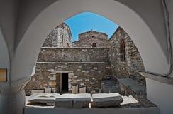 Una chiesa di 100 porte osservate attraverso la finestra incurvata a Parikia, Paros, Grecia Immagine Stock