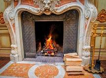Una chimenea clásica del estilo con leña ardiente Foto de archivo libre de regalías