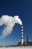 Una chimenea que fuma a la derecha en el cielo azul Foto de archivo