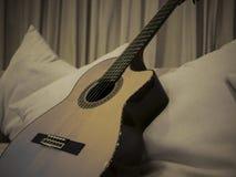Una chitarra classica adorabile su uno strato bianco Fotografia Stock