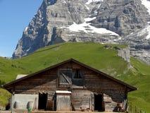 Una choza de la montaña y las montañas suizas en el fondo foto de archivo