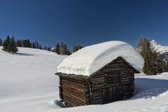 Una choza de madera de la cabina en el fondo de la nieve del invierno Fotos de archivo libres de regalías