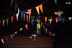 Una cinta con las banderas coloreadas bajo techo de madera en el barra-restaurante Imagen de archivo
