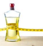 Una cinta de medición alrededor de una botella de aceite de oliva Imágenes de archivo libres de regalías