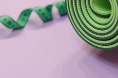 Una cinta métrica verde torcida en un espiral y una estera para el fitne fotos de archivo