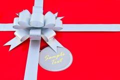 Una cinta y un arqueamiento de plata en fondo rojo Fotos de archivo libres de regalías
