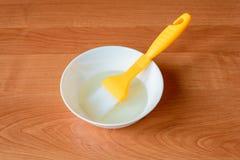 Una ciotola bianca con olio che si trova su una tavola di legno con una spazzola di pasticceria Immagine Stock Libera da Diritti