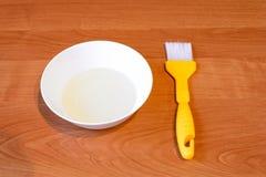 Una ciotola bianca con olio che si trova su una tavola di legno con una spazzola di pasticceria Fotografie Stock Libere da Diritti