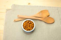 Una ciotola ceramica blu con le mandorle, un cucchiaio di legno e la spatola Fotografia Stock