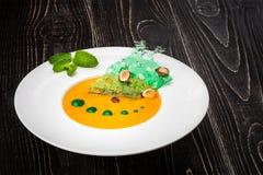 Una ciotola con la minestra della zucca su un fondo di legno nero Alimentazione costante dal cuoco unico Fotografia Stock