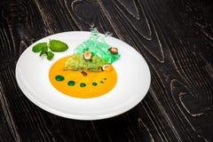Una ciotola con la minestra della zucca su un fondo di legno nero Alimentazione costante dal cuoco unico Fotografie Stock