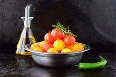 Una ciotola del metallo con i pomodori ciliegia gialli e rossi con il ramo dei rosmarini freschi e di un barattolo di vetro di ol Fotografie Stock Libere da Diritti