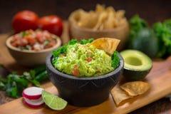 Una ciotola deliziosa di guacamole accanto agli ingredienti freschi su una tavola con le patatine fritte e la salsa di tortiglia Fotografie Stock