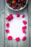 Una ciotola di ciliege ed e di rose rosse su fondo di legno Immagini Stock