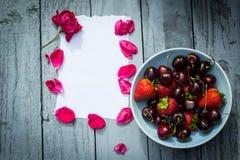 Una ciotola di ciliege ed e di rose rosse su fondo di legno Fotografie Stock