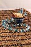 Una ciotola di fiocchi di granturco e serie di perle Immagine Stock