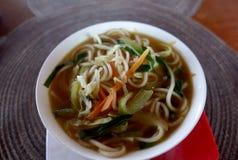 Una ciotola di minestra con le tagliatelle e le verdure su un tovagliolo rotondo Fotografia Stock Libera da Diritti