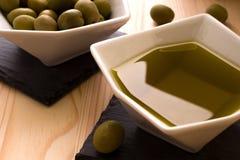 Una ciotola di olio d'oliva con le olive nei precedenti Fotografia Stock Libera da Diritti