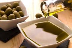 Una ciotola di olio d'oliva con le olive nei precedenti Immagini Stock Libere da Diritti