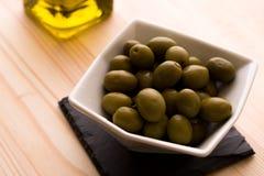 Una ciotola di olive con l'olio d'oliva imbottiglia i precedenti Fotografie Stock