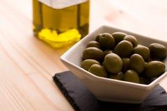 Una ciotola di olive con l'olio d'oliva imbottiglia i precedenti Immagini Stock