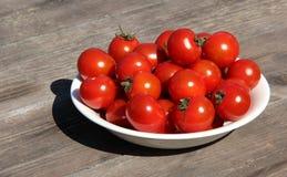 Una ciotola di pomodori freschi su una tavola di legno al sole Immagini Stock