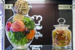 Una ciotola di vetro di frutta e di barattolo di pasta all'interno del caffè immagini stock