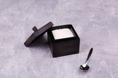 Una ciotola di zucchero nera con un cucchiaio fotografia stock