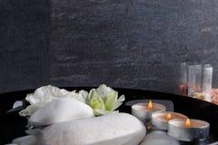 In una ciotola profonda con acqua è un ciottolo, l'aroma delle candele ed i germogli dei fiori colorati Immagine Stock