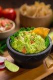 Una ciotola verticale deliziosa del colpo di guacamole accanto agli ingredienti freschi su una tavola con le patatine fritte e la Fotografie Stock Libere da Diritti