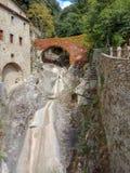Una ciudad de piedra muy pequeña con una cascada sin el agua fotos de archivo