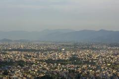 Una ciudad en un valle enorme en un fondo de siluetas de montañas debajo del cielo pesado foto de archivo