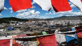 Una ciudad que mira a través de bandera tibetana colorida del talismán imágenes de archivo libres de regalías