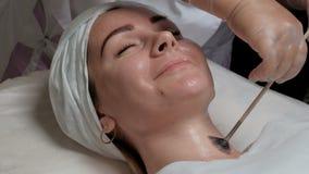Una clase de manos femeninas en guantes, manchada con una crema cosmética del cepillo en el cuello del ` s de la mujer Muchacha b almacen de video