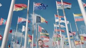 Una clip ottimista dell'unità di tutti i paesi e nazioni e di un futuro luminoso contro lo sfondo delle bandiere di stock footage