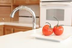 Una cocina blanca limpia con dos tomates rojos Fotografía de archivo libre de regalías