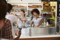 Una coda dei clienti è servito da due donne ad una barra del panino immagine stock libera da diritti