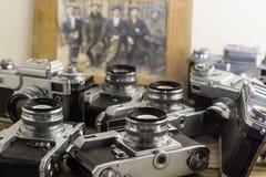 Una colección de cámaras viejas con una foto del vintage en un fondo de madera imagenes de archivo