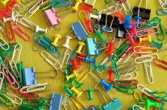 Una colección de clips de papel, de clips de la carpeta y de pernos del empuje Imagen de archivo libre de regalías