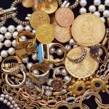 Una colección de joyas y de monedas de oro en el terciopelo negro fotografía de archivo