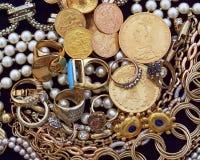 Una colección de joyas y de monedas de oro en el terciopelo negro imágenes de archivo libres de regalías