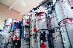 Una colección de latas de la pintura, de cubos del pegamento, de masilla y de material tóxico y peligroso apilados imagenes de archivo
