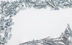 Una colección de tornillos, de nueces, de clavos y de arandelas de cierre del hierro por encima y por debajo de Imágenes de archivo libres de regalías