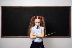 Una colegiala de la muchacha se est? colocando en el consejo escolar y est? sosteniendo un indicador imagen de archivo