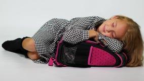 Una colegiala duerme en una mochila y sonríe dulce almacen de video