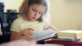 Una colegiala lee los libros mientras que se sienta en una tabla El enseñar casero Educación de niños Día de conocimiento almacen de metraje de vídeo
