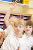 Una colegiala levanta su mano en una clase primaria Fotografía de archivo libre de regalías