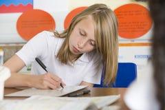 Una colegiala que estudia en clase Foto de archivo