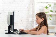 Una colegiala que trabaja en un ordenador Foto de archivo libre de regalías